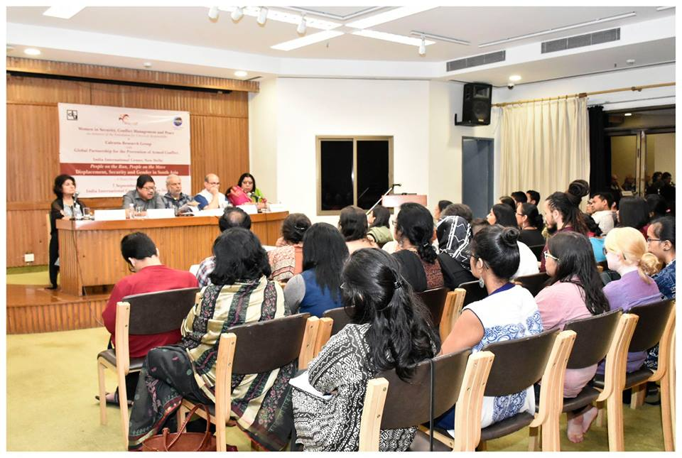 Panelists speak to an audience at a conference.